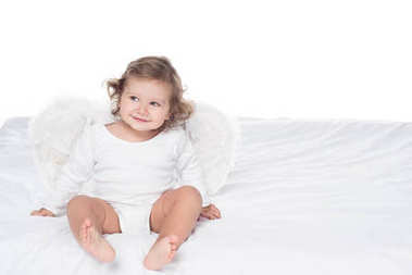 adorable smiling baby with wings sitting on bed, isolated on white