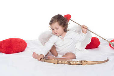 Little cherub sitting on bed with bow and arrow, isolated on white stock vector