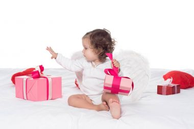 Cute baby angel sitting on bed with presents, isolated on white stock vector