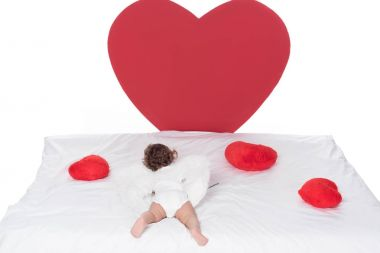 Little cupid with wings lying on bed with hearts, isolated on white stock vector