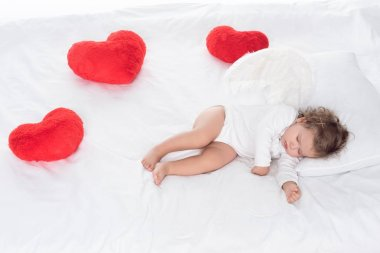 Little angel with wings lying on bed with hearts stock vector