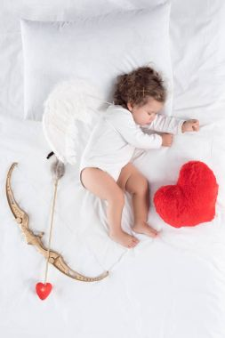 little baby with wings lying on bed with heart pillow, bow and arrow