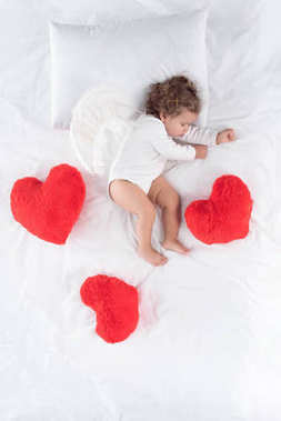 Little cupid with wings lying on bed with red hearts stock vector