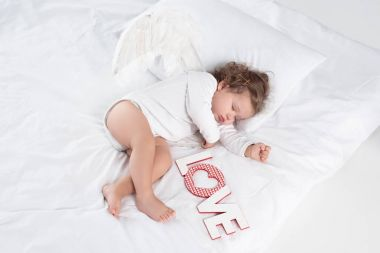 little cherub with wings lying on bed with love sign