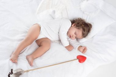 Little cupid with wings sleeping on bed with arrow stock vector