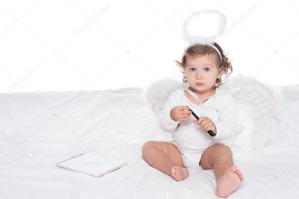 little angel with wings and nimbus on bed with notepad, isolated on white