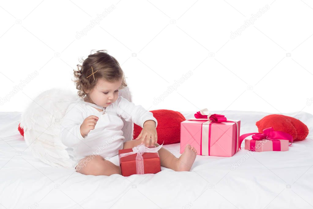 little cherub sitting on bed with gift boxes, isolated on white
