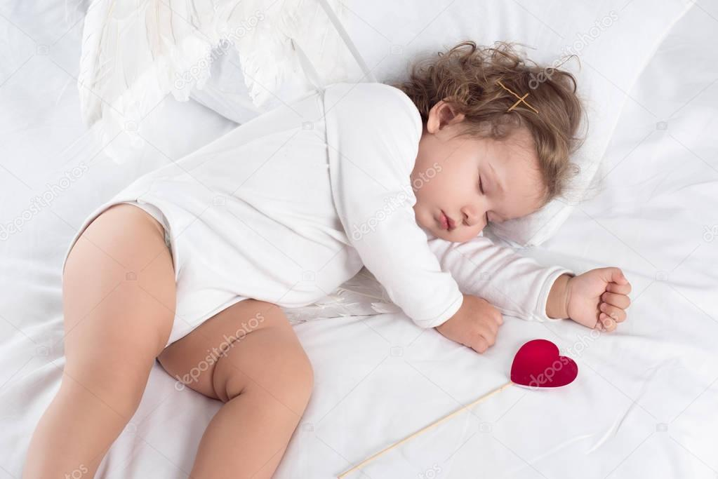 cute cherub with wings lying on bed with heart