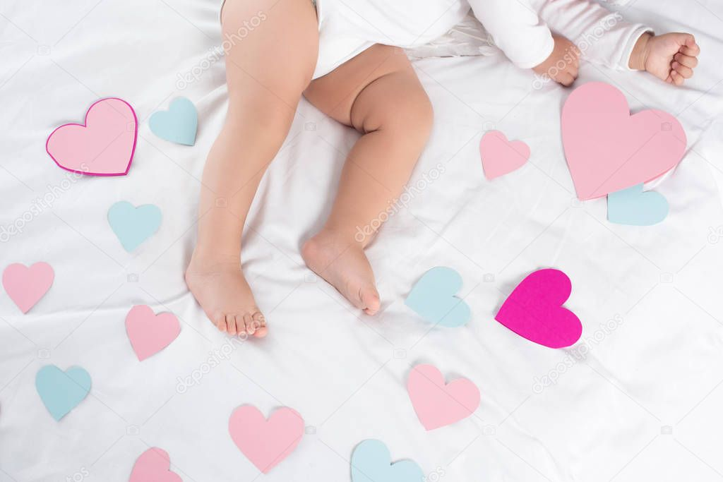 cropped view of little baby lying on bed with hearts