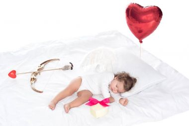 Little cherub with wings lying on bed with heart balloon, present, bow and arrow, isolated on white stock vector