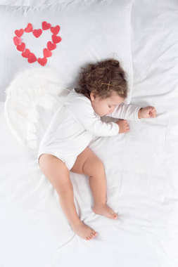 adorable cupid with wings sleeping on bed with red hearts