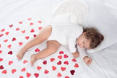 little cupid with wings sleeping on bed with red hearts