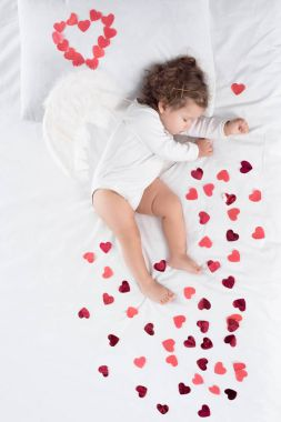 little toddler with wings sleeping on bed with red hearts