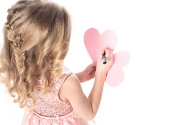 blonde child writing valentines greeting card, isolated on white