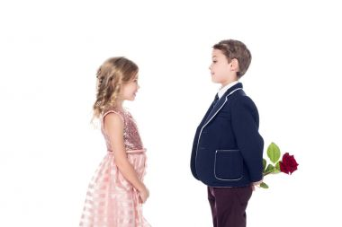 side view of fashionable boy in suit holding rose flower and looking at adorable little girl in pink dress isolated on white