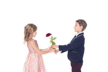 side view of adorable stylish children holding rose flower and looking at each other isolated on white