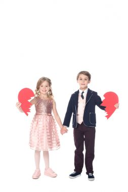 beautiful little children holding pieces of broken heart symbol and smiling at camera isolated on white