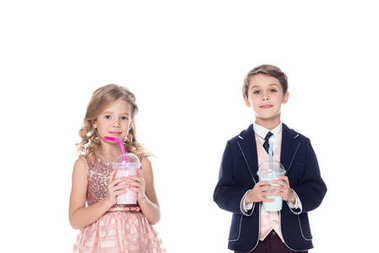 adorable little kids holding milkshakes in plastic cups and smiling at camera isolated on white