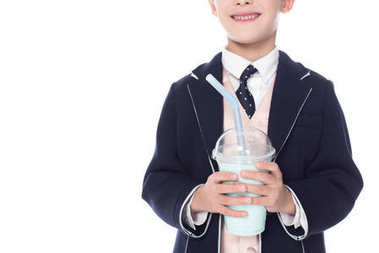 cropped shot of smiling little boy in suit holding milkshake in plastic cup isolated on white
