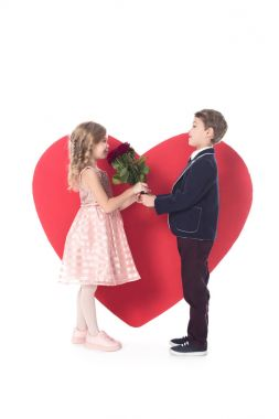 side view of cute little boy presenting flowers to adorable little girl and big red heart symbol behind isolated on white