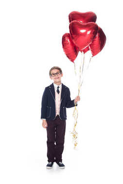 Cute little boy in suit and eyeglasses holding red heart shaped balloons and smiling at camera isolated on white stock vector