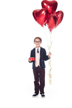 adorable smiling little boy in suit and eyeglasses holding red heart shaped balloons and gift box isolated on white