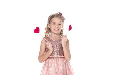 beautiful little kid in pink dress holding red hearts on sticks and smiling at camera isolated on white