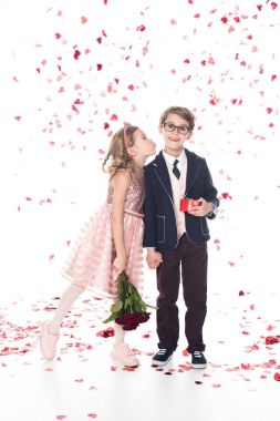 Cute little boy in eyeglasses and suit holding gift box and smiling at camera while girl with roses able to kiss him on white with falling heart shaped confetti stock vector