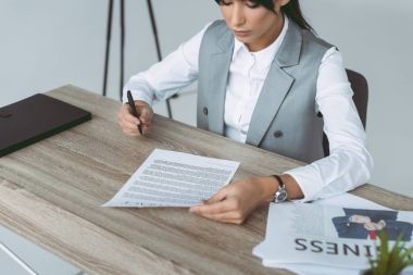 cropped image of businesswoman signing contract isolated on gray