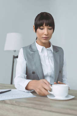 attractive businesswoman taking cup isolated on gray