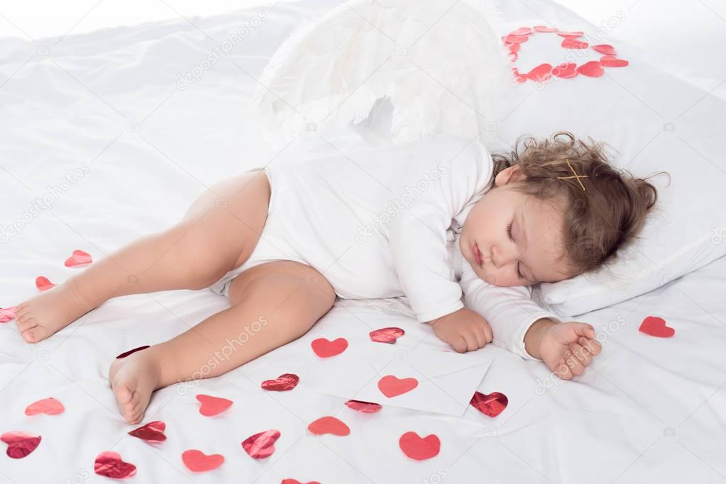 little sleepy cherub with wings lying on bed with hearts