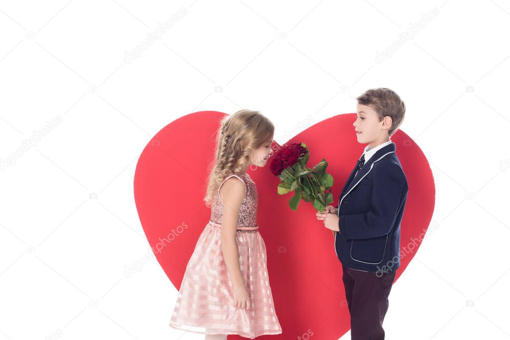 side view of little boy presenting flowers to beautiful little girl and big red heart symbol behind isolated on white