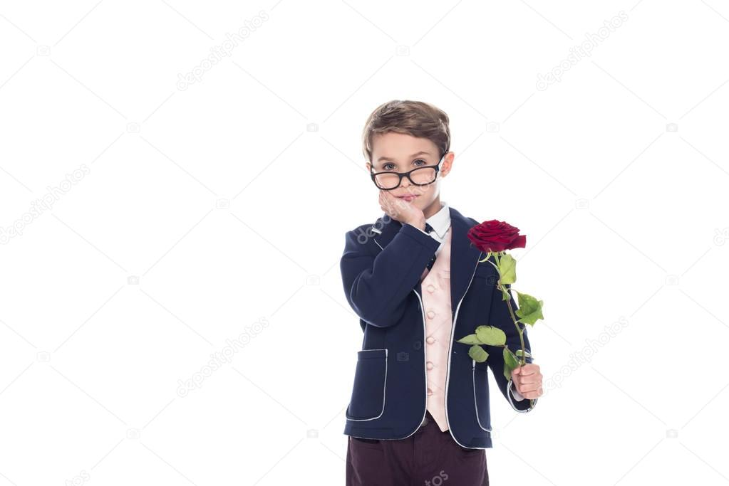 serious little boy in suit and eyeglasses holding rose flower and looking at camera isolated on white