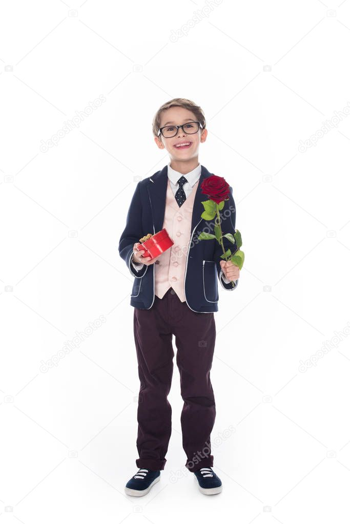 cute little boy in suit and eyeglasses holding rose flower and heart shaped red gift box isolated on white