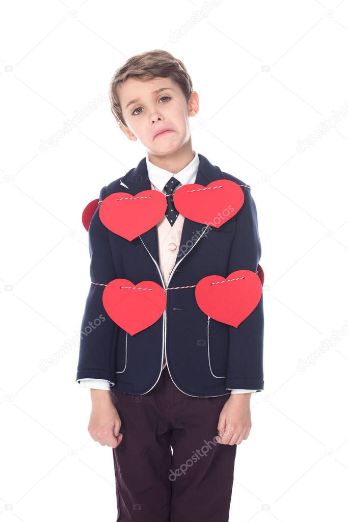 upset little boy in suit staying tied with rope and red hearts, looking at camera isolated on white