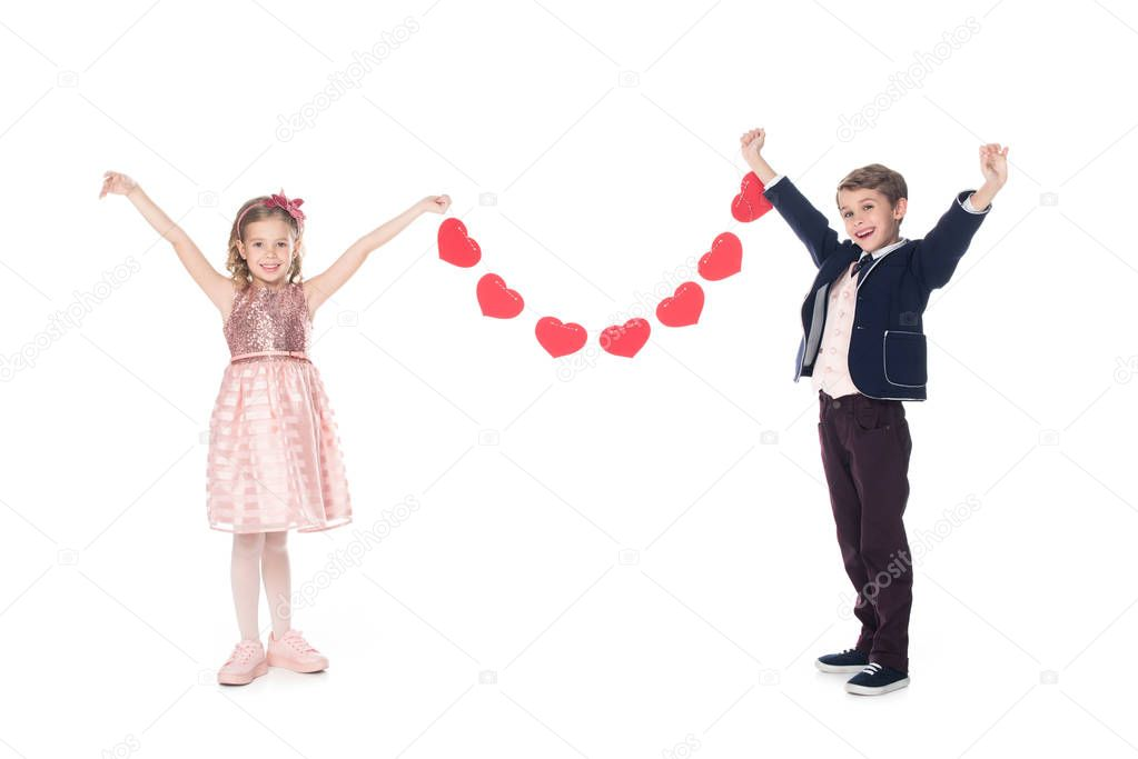 happy stylish children holding red hearts and smiling at camera isolated on white