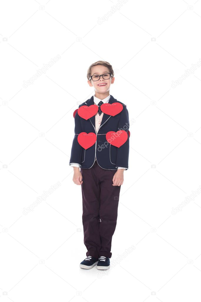 cute smiling little boy in suit and eyeglasses staying tied with rope and red hearts isolated on white