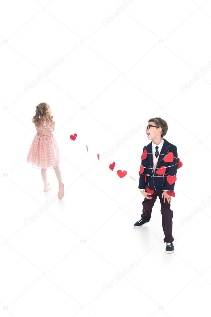 little girl tying stylish boy with rope and red hearts isolated on white