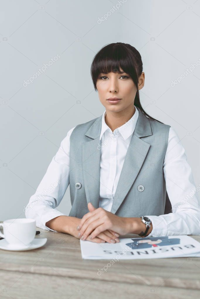 beautiful businesswoman sitting at table and looking at camera isolated on gray