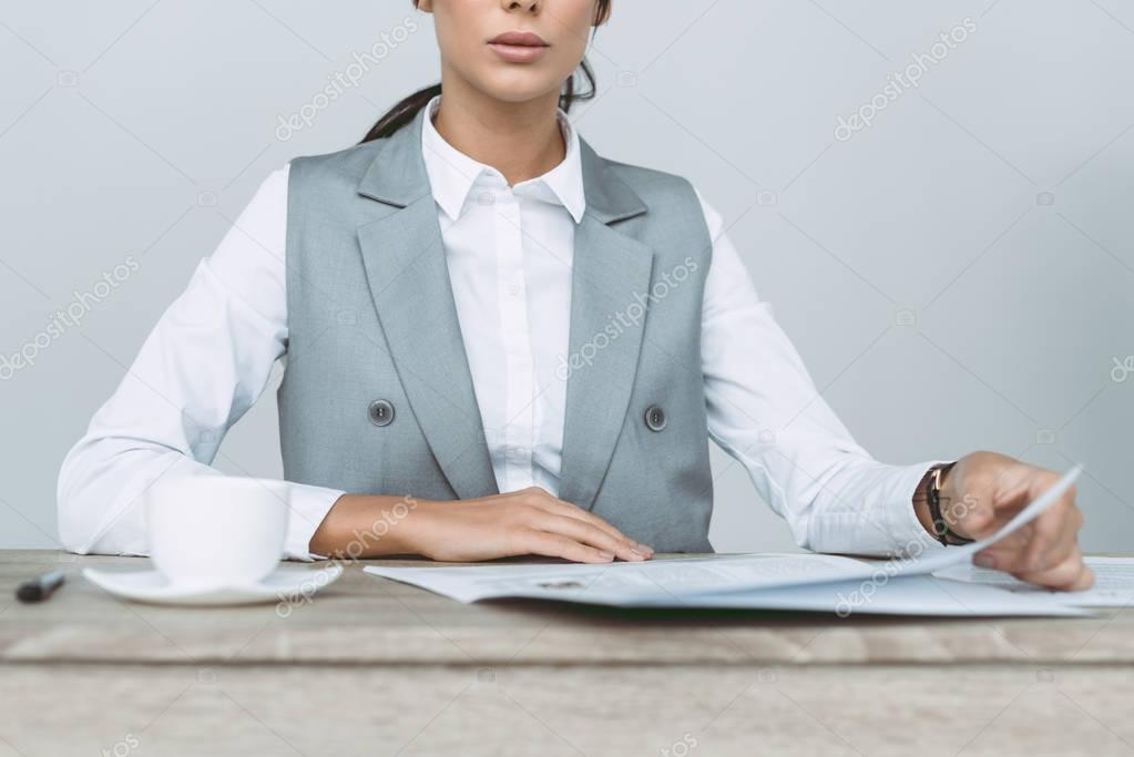 cropped image of businesswoman reading newspaper isolated on gray