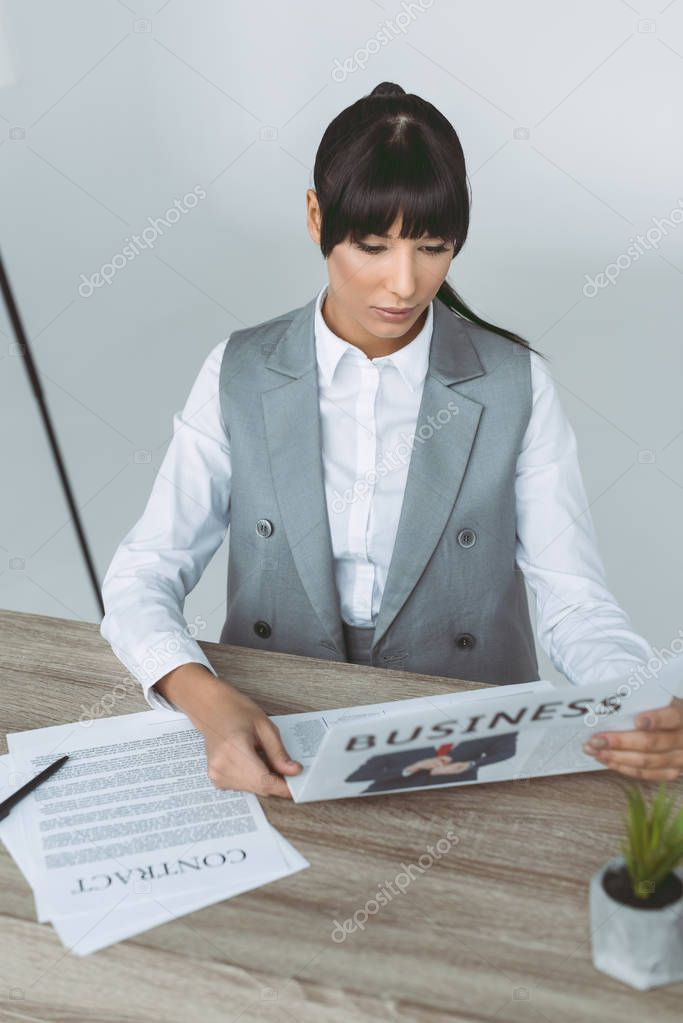 businesswoman reading newspaper isolated on gray
