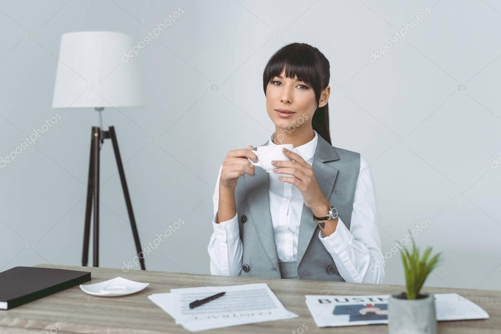 smiling businesswoman holding cup isolated on gray