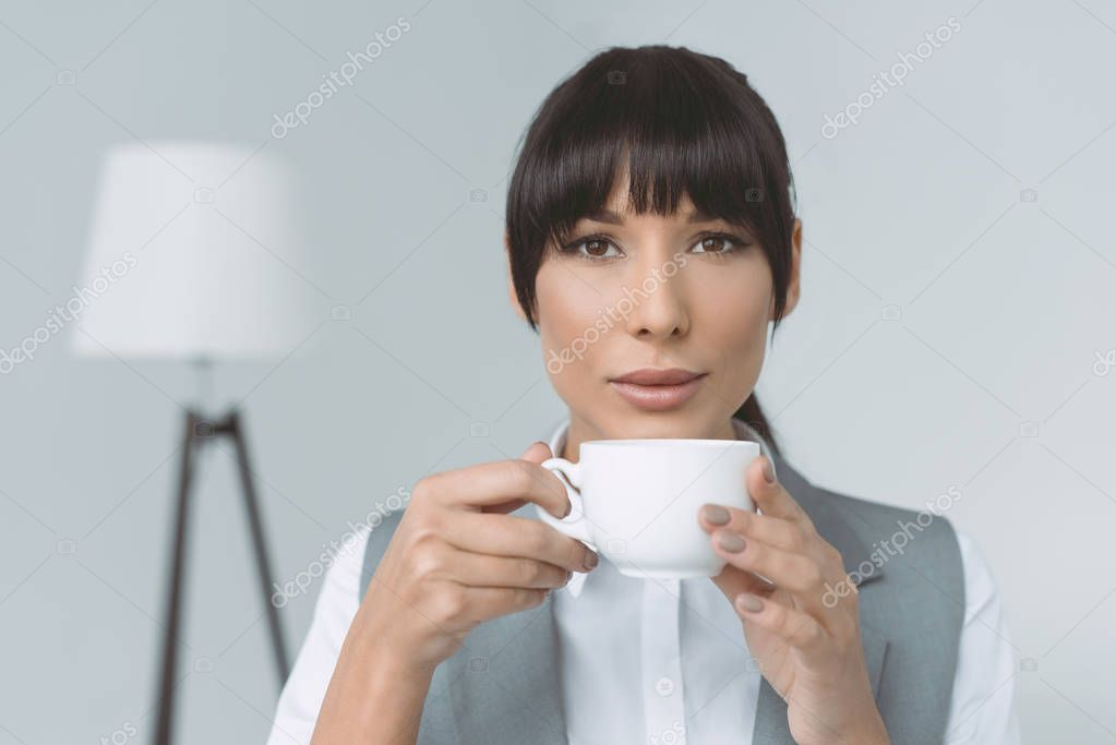 attractive businesswoman drinking coffee and looking at camera isolated on gray