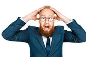 scared bearded businessman in eyeglasses holding hands on head isolated on white