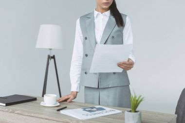 cropped image of businesswoman holding document isolated on gray
