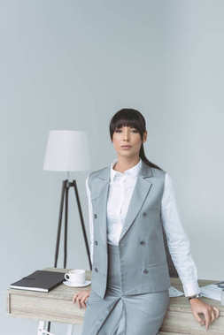 attractive businesswoman leaning on table and looking at camera isolated on gray