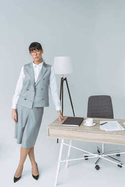 businesswoman standing at table and looking at camera isolated on gray