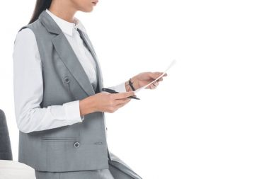 cropped image of businesswoman leaning on table and holding documents isolated on white