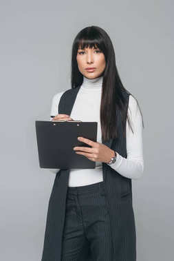 businesswoman standing with clipboard and looking at camera isolated on gray