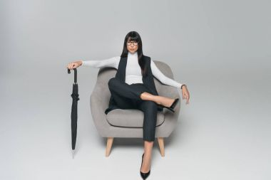 beautiful brunette businesswoman sitting on armchair with umbrella on gray